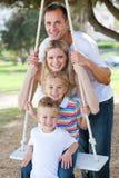 Familia feliz que juega en un oscilación Imagenes de archivo