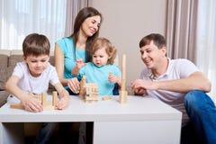 Familia feliz que juega junto en casa Foto de archivo