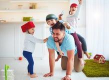 Familia feliz que juega junto en casa, montando en padre fotos de archivo