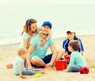 Familia feliz que juega junto en la playa arenosa Fotos de archivo libres de regalías