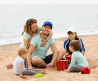 Familia feliz que juega junto en la playa arenosa Fotos de archivo