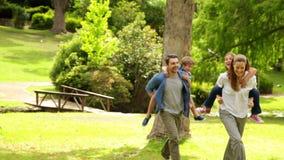 Familia feliz que juega la persecución en el parque junto almacen de metraje de vídeo