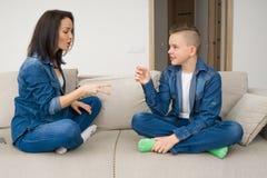 Familia feliz que juega las tijeras de papel de la roca en casa Imagen de archivo libre de regalías