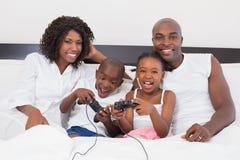 Familia feliz que juega a los videojuegos juntos en cama Imágenes de archivo libres de regalías