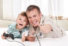 Familia feliz que juega a un juego video Fotografía de archivo