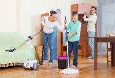 Familia feliz que limpia con la aspiradora en casa Fotografía de archivo