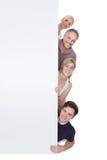 Familia feliz que lleva a cabo el cartel en blanco Imágenes de archivo libres de regalías