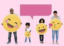 Familia feliz que lleva a cabo iconos del emoji fotografía de archivo