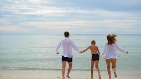 Familia feliz que lleva a cabo las manos que corren a lo largo de la orilla Para correr en crear del agua salpica almacen de video