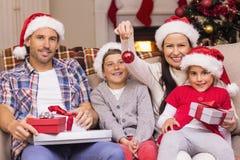 Familia feliz que lleva el sombrero de santa en el sofá Imágenes de archivo libres de regalías