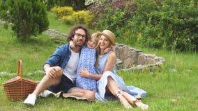 Familia feliz que merienda en el campo al aire libre con su hija linda, ropa azul, mujer en sombrero almacen de metraje de vídeo