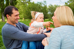 Familia feliz que merienda en el campo en el parque Pla de alimentación de la madre de la hija Fotografía de archivo libre de regalías