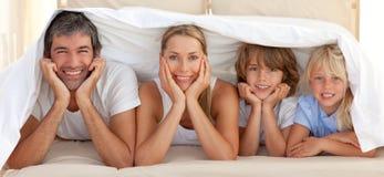 Familia feliz que miente bajo una manta Imagen de archivo libre de regalías