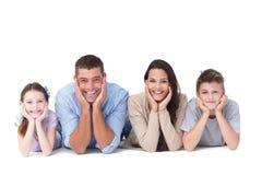 Familia feliz que miente con la cabeza en manos Foto de archivo