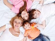 Familia feliz que miente en cama Fotografía de archivo libre de regalías