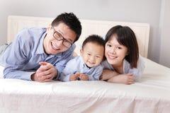 Familia feliz que miente en cama Imágenes de archivo libres de regalías