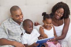 Familia feliz que miente en cama usando la PC de la tableta Imágenes de archivo libres de regalías