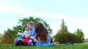 Familia feliz que miente en el césped La madre y el padre que juegan con su hijo, el niño sonríe Contra la perspectiva de almacen de metraje de vídeo