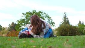 Familia feliz que miente en el césped La madre y el padre que juegan con su hijo, el niño sonríe Contra la perspectiva de almacen de video