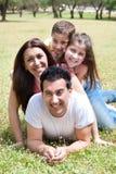 Familia feliz que miente en el campo de hierba Fotografía de archivo