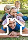 Familia feliz que miente en el parque sobrepuesto con forma de la casa imágenes de archivo libres de regalías