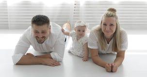 Familia feliz que miente en el piso blanco en la sala de estar metrajes