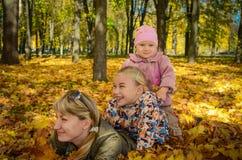 Familia feliz que miente en hojas de otoño Foto de archivo libre de regalías