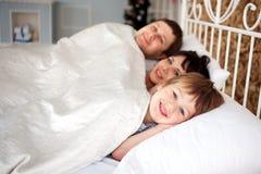 Familia feliz que miente en la cama, concepto de familia. Foto de archivo libre de regalías