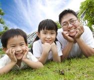 Familia feliz que miente en la hierba Foto de archivo libre de regalías