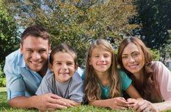 Familia feliz que miente en la hierba Imágenes de archivo libres de regalías