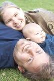 Familia feliz que miente en la hierba Imagen de archivo libre de regalías