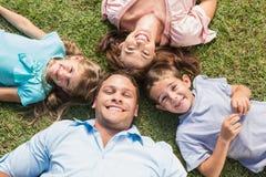 Familia feliz que miente en la hierba en un círculo Imágenes de archivo libres de regalías