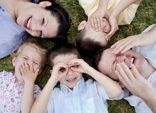 Familia feliz que miente en la tierra fotos de archivo libres de regalías