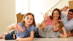 Familia feliz que miente en piso en su nuevo hogar que agita en la cámara almacen de metraje de vídeo