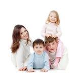 Familia feliz que miente en suelo en estudio Foto de archivo