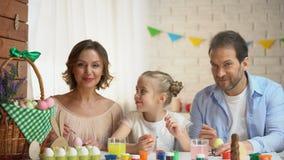 Familia feliz que mira en cámara y que sonríe, huevos que colorean, preparación de Pascua almacen de metraje de vídeo