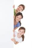 Familia feliz que mira a escondidas de la cartelera en blanco imagen de archivo