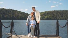 Familia feliz que mira la cámara mientras que presenta en el embarcadero en el lago reservado metrajes