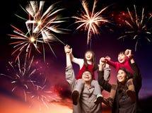 Familia feliz que mira los fuegos artificiales Fotos de archivo libres de regalías