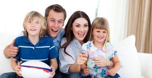 Familia feliz que mira un emparejamiento del rugbi Fotografía de archivo