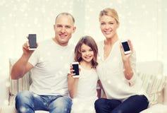 Familia feliz que muestra a smartphones las pantallas en blanco Fotografía de archivo libre de regalías