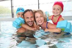 Familia feliz que pasa buen tiempo en piscina Imagen de archivo libre de regalías