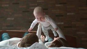 Familia feliz que pasa el tiempo junto en la hora de acostarse que juega y que abraza almacen de metraje de vídeo