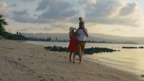 Familia feliz que pasa tiempo en la playa con un bebé el vacaciones metrajes