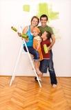 Familia feliz que pinta su nuevo hogar junto Imagen de archivo libre de regalías