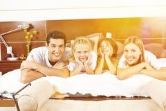 Familia feliz que pone en cama con los niños Foto de archivo