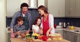 Familia feliz que prepara verduras juntas metrajes