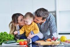 Familia feliz que prepara verduras juntas en casa en la cocina fotos de archivo libres de regalías