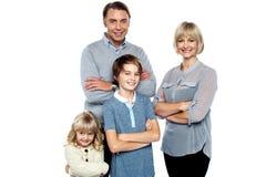 Familia feliz que presenta con los brazos cruzados fotos de archivo libres de regalías