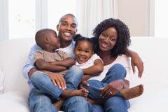 Familia feliz que presenta en el sofá junto imagen de archivo